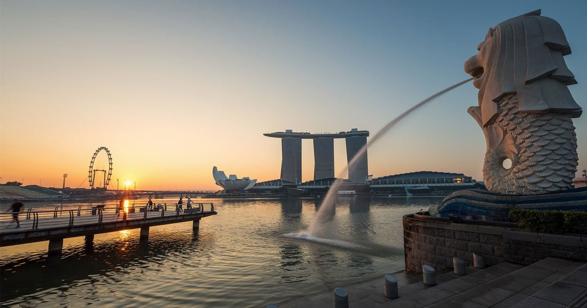 The sun rises over a peaceful day in Singapore, beside the famous merlion.
