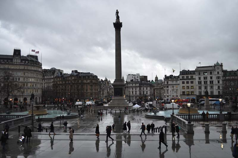People walk about in Trafalgar Square in London