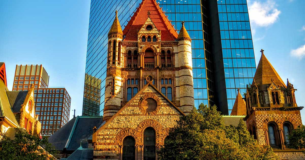 A high rise office building looms over a church in Boston near Harvard University.