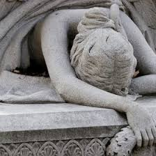 A stone sculpture of a woman collapsed