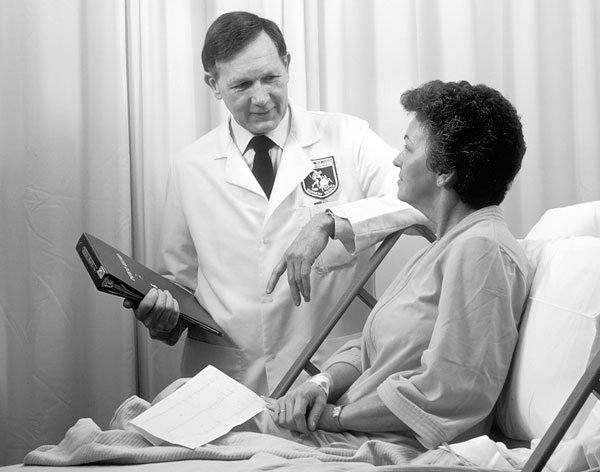 Oncology doctor consults with a patient at her bedside (black and white)