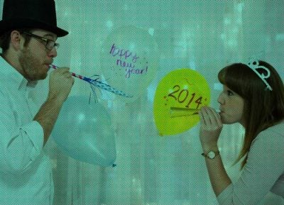 Two people blow celebratory horns brining in the 2014 new year