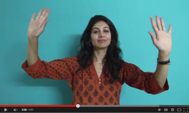 A woman lifts up her hands while singing to verse to a song about gratitude