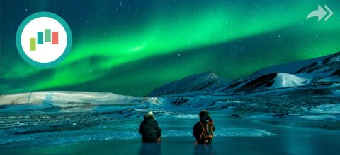 Two women stand in freezing ocean water watching the aurora borealis, experiencing awe.