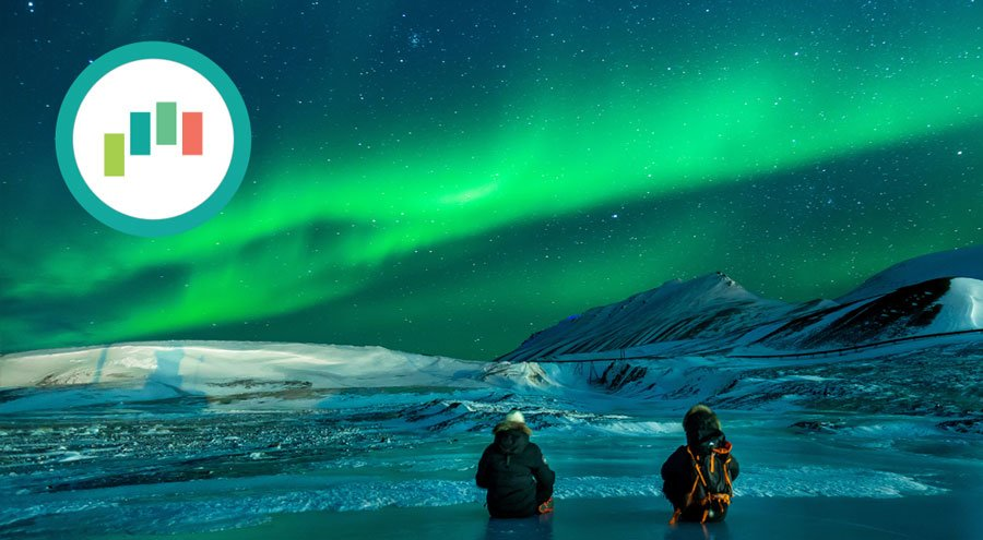 The aurora borealis lights up the night sky while two women stand in freezing ocean water in the arctic ocean, experiencing awe.