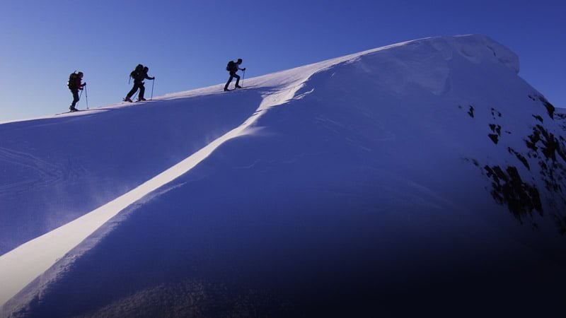 A team of mountain climbers approaches the peak of a snow covered mountain.