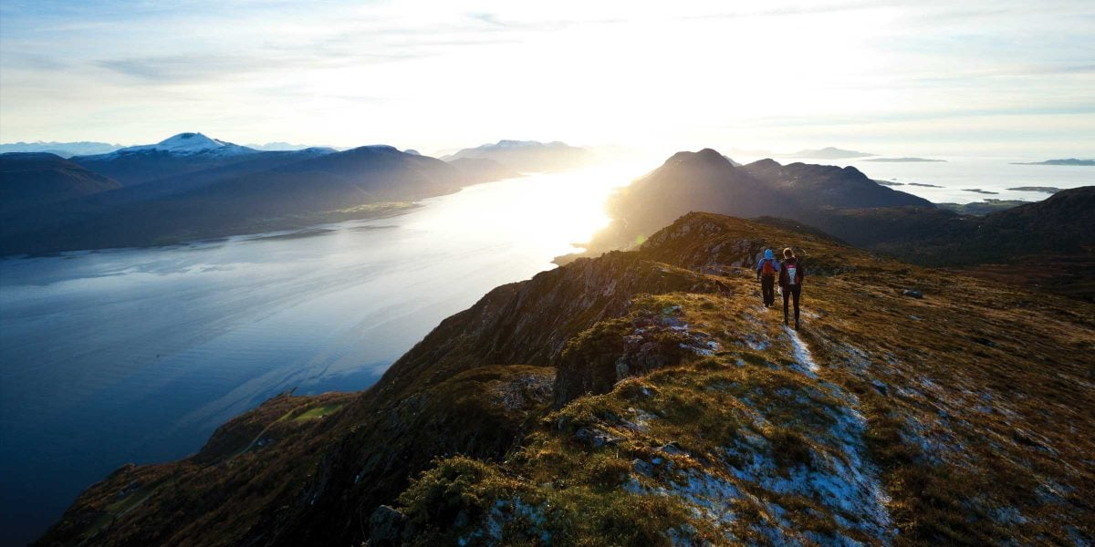 Two hikers walk over a rise overlooking a long lake and sunrise, with mountains in the background.