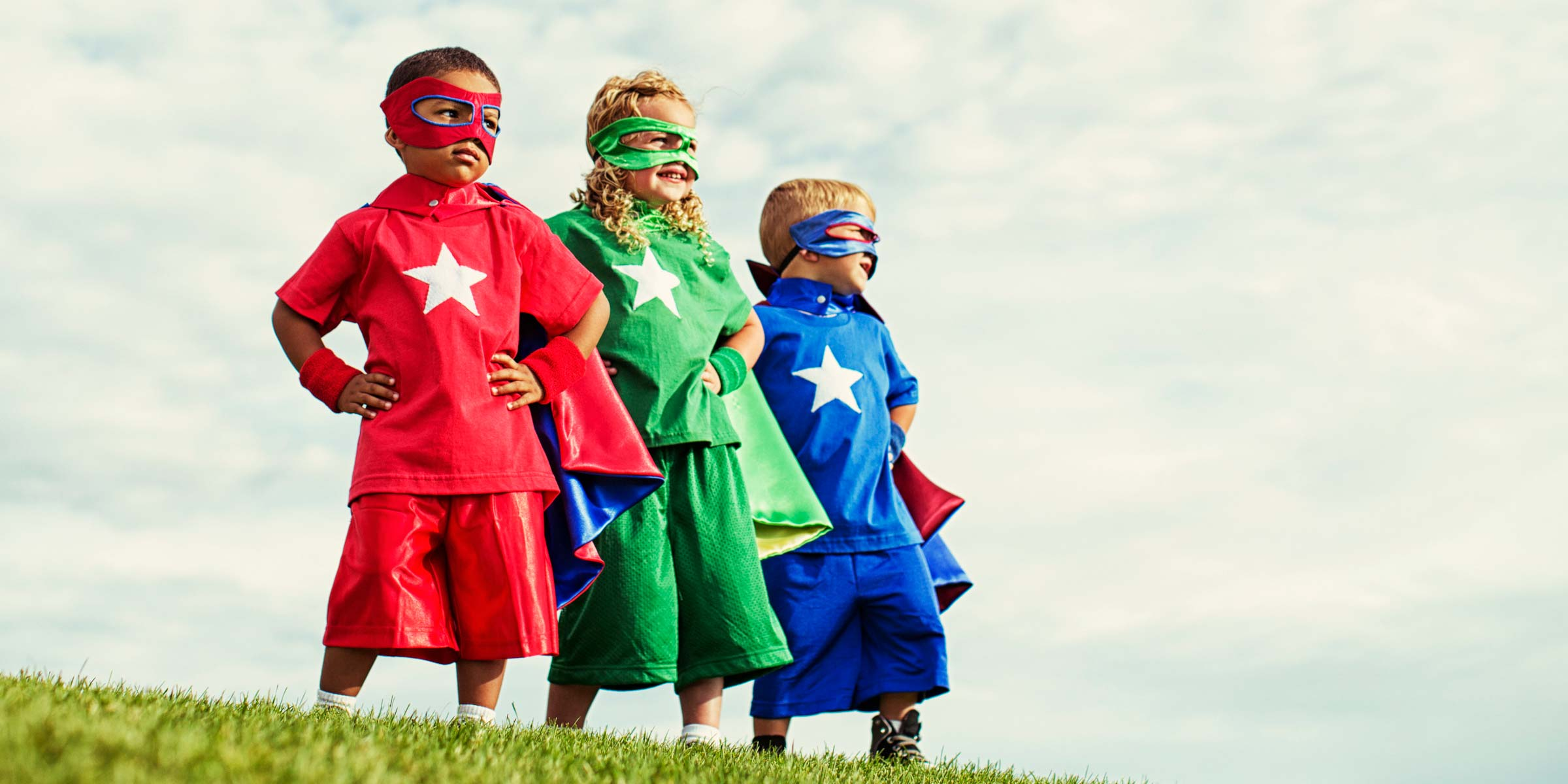 Three small children line up in super hero costumes on the hill.