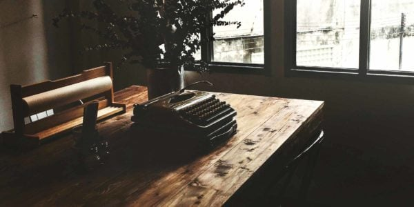 A typewriter sits on a table in the sunlight