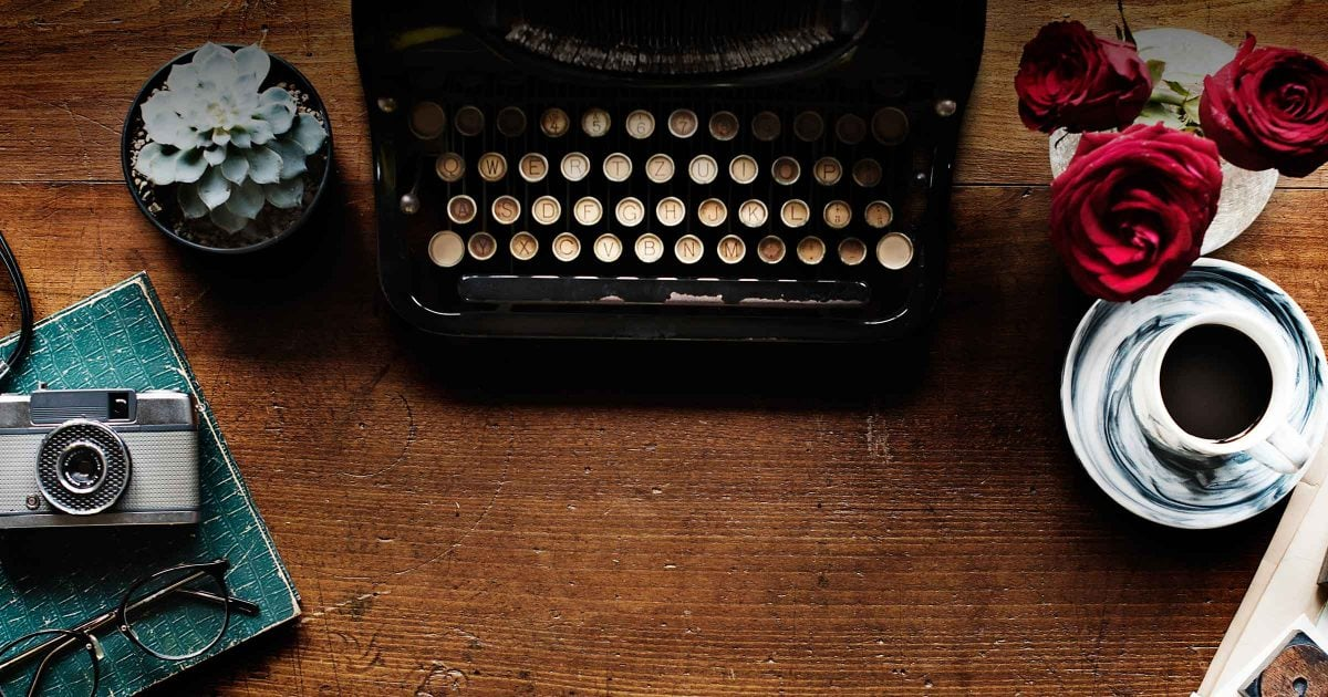 A typewriter sits on a desk, surrounded by other human interest artifacts, like coffee and a camera and flowers.