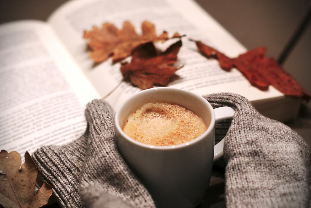 A latte rests beside a sweater and a book, maybe a journal, with some leaves on top.