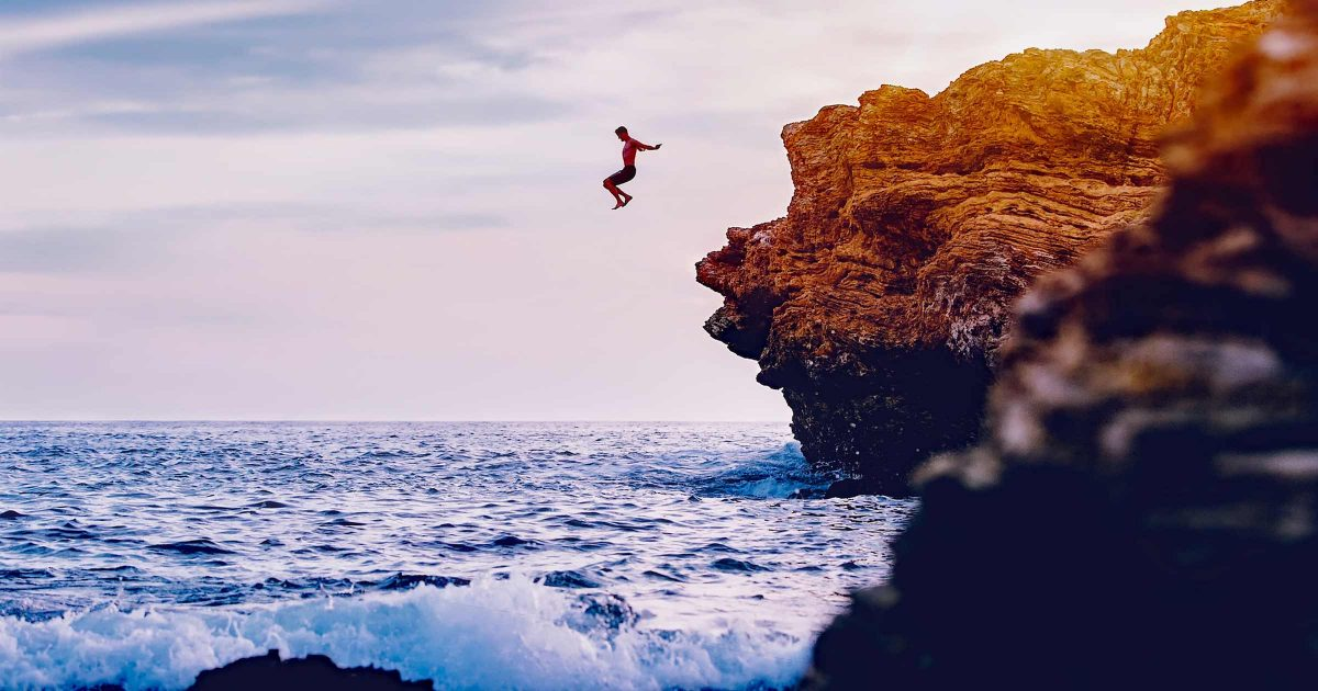A person jumps off of a high cliff into a cool blue ocean during twilight.