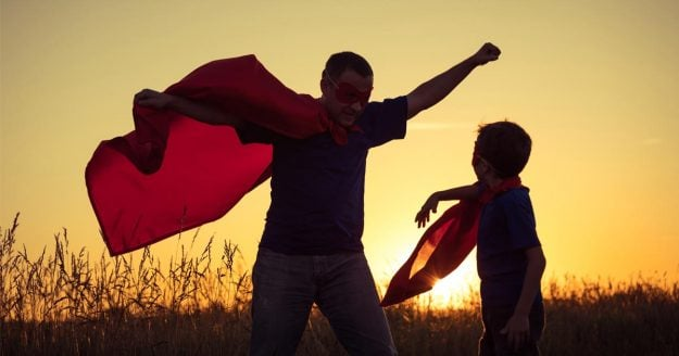 A father and son play in a field at sunset, wearing their capes and acting out superhero-hood!
