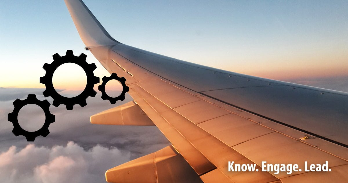 A plane wing as seen from the airplane window with some illustrated gears over top.