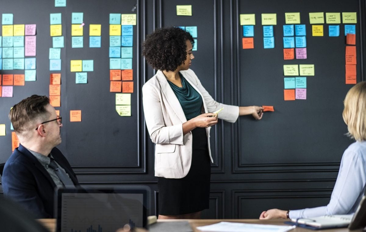A woman stands in front of a black wall covered in colourful post-it noes with two people sitting on either side of her. All look engaged as she moves a note on the wall.