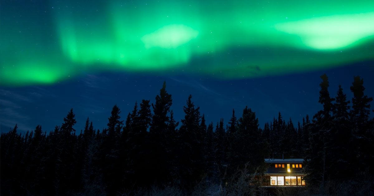 The aurora borealis lights up a night time sky over a forest and a brightly lit house.