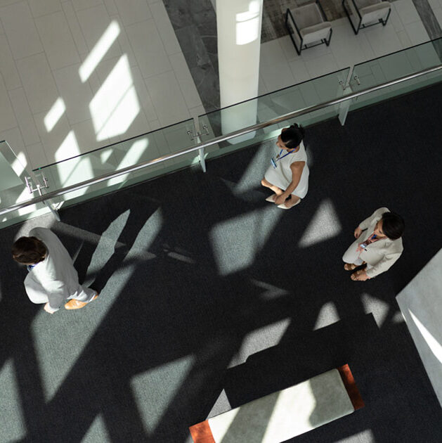 People in an office walk down the hallway as seen from above, with a webinar icon and EITC logo.