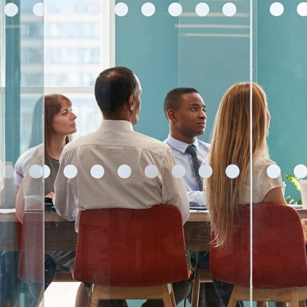 A team meets about an important issue and look up at an unseen leader who is presenting at the front of the room.
