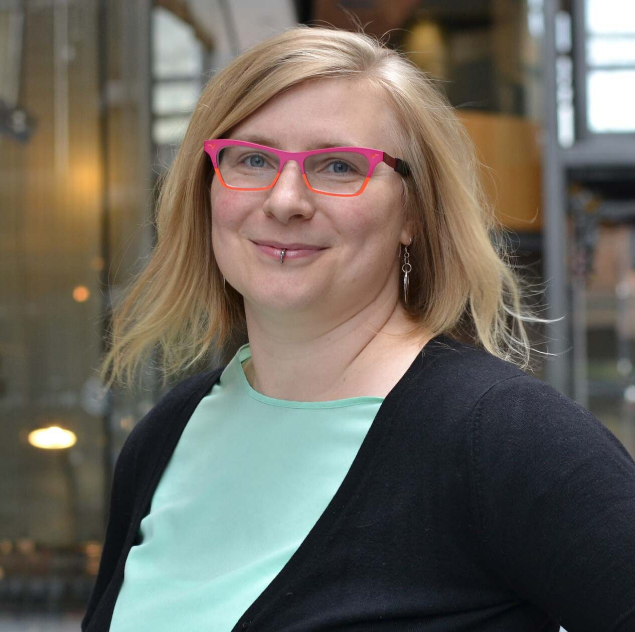Rebecca Cory: a white woman in her thirties wears a black cardigan over a mint blouse and wears her pink and orang glasses.